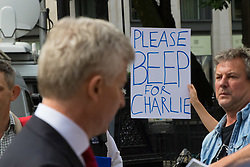 London, July 13th 2017. The parents of terminally ill Charlie Gard, Chris Gard and Connie Yates arrive at the High Court in London in a last ditch attempt to seek permission from the court to seek alternative treatment for their son's condition, Mitochondrian DNA depletion syndrome. PICTURED: A family representative addresses the media as a protester's banner asks passing drivers to 'Beep for Charlie'..