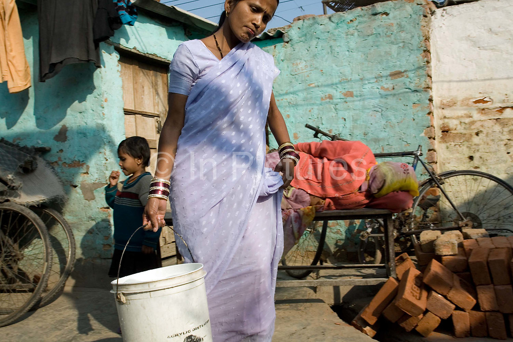 A woman carries water delivered by tanker back to her home in the slum of Kusumpur Pahari. The slum, built more than thirty years ago has no running water or sewage facilities. The only water supply come from the Municipal  JAL Board water trucks that visit several times a day. The deliveries are supposed to be free but in reality, residents must pay bribes to have the water delivered.