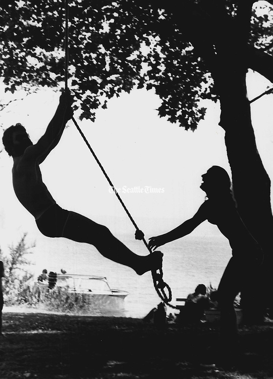 A couple in silhouette shared a rope swing near the beach. (Peter Liddell / The Seattle Times, 1970)