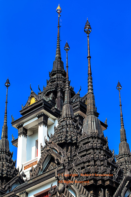 Spire Stacking: Ornate, multi tiered; black spires are seemingly stacked one upon the other while set against a clear blue sky, Wat Ratchanatdaram, Bangkok Thailand.