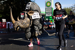 © Licensed to London News Pictures. 03/10/2021. London, UK. A woman wears a rhino costume as she passes through Greenwich as part of the 2021 London Marathon.This London Marathon will be the first full scale staging of the race in more than two years due to the Coronavirus Pandemic.  Photo credit: George Cracknell Wright/LNP