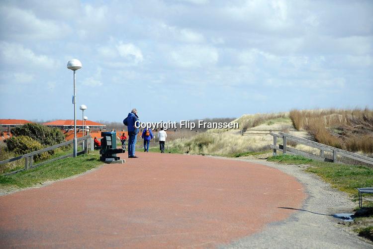 Nederland, Westkapelle, 14-9-2014 De kunstmatige zeewering van dit deel van de zeeuwse kust is de hoogste van het land. De zeedijk is aangelegd na de watersnoodramp in 1953, ter vervanging van de zwakke duinen en moet zeeland behoeden voor overstroming tijdens storm en hoogwater of springvloed.Wandelaars lopen via de zeewering de duinen in . The artificial seawall of this part of the zeeuwse coast is the highest in the country. The dike was built after the flood in 1953, replacing the fragile dunes and protect Zealand for flooding during storms and high water or springtide. Foto: Flip Franssen