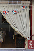 Union Jack flags hang in the window of a tea shop, on 11th September 2018, in Ludlow, Shropshire, England UK.