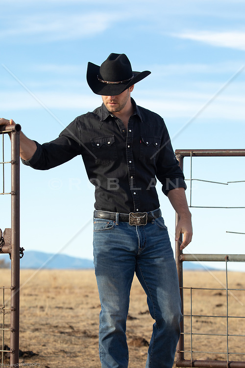 cowboy opening up a rustic gate on a ranch
