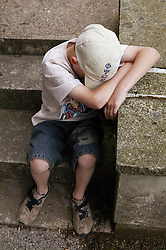 Boy sitting on steps with his head bowed,