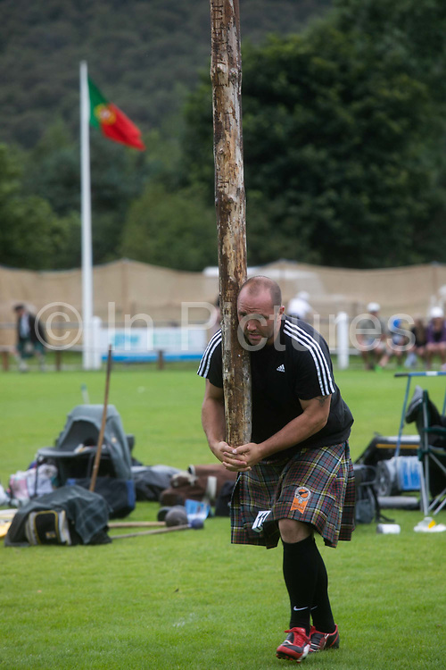 Highland Games, 3rd of August 2019, Newtonmore, Scotland, United Kingdom. A strong man compete in the caber tossing competition. The Highland Games is a traditional annual event where competitors compete as strong men, runners, dancers, pipers and at tug-of-war. The games go back centuries and are happening through-out the summer across Scotland. The games are both an important event locally and a global tourist attraction.