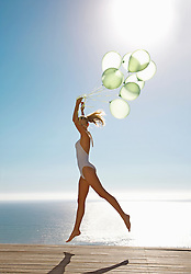 Profile of a woman jumping mid air holding a bundle of green balloons