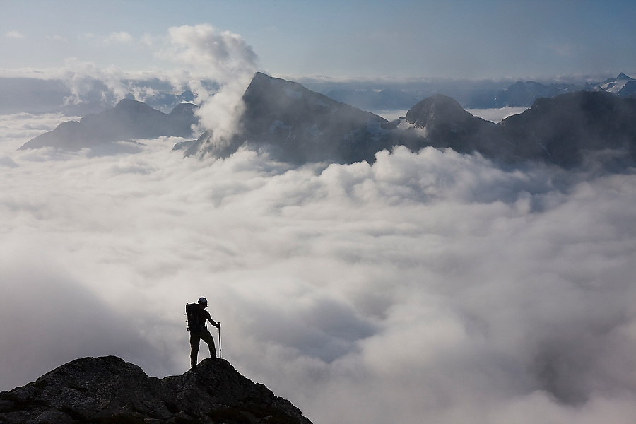 Jim Prager looks down into the cloud-filled valley below on the descent from Luna Col to Access Creek, Northern Picket Range, North Cascades National Park, Washington.