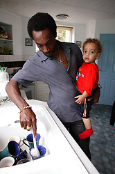 Father washing dishes and minding his young son,