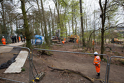 Wendover, UK. 28th April, 2021. HS2 security guards observe a large mechanical digger being used for the 'translocation' of soil as an environmental mitigation measure for the HS2 high-speed rail link in ancient woodland at Jones Hill Wood in the Chilterns AONB. Felling of the woodland which contains resting places and/or breeding sites for pipistrelle, barbastelle, noctule, brown long-eared and natterer's bats has recommenced after a High Court judge yesterday refused campaigner Mark Keir permission to apply for judicial review and lifted an injunction on felling.