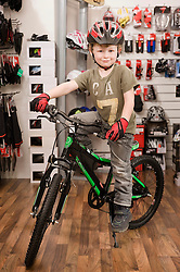 Boy with bicycle helmet in bike shop