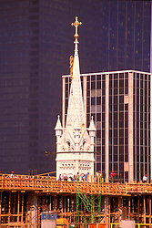 Stock photo of a church steeple rising above construction in downtown Houston, Texas.
