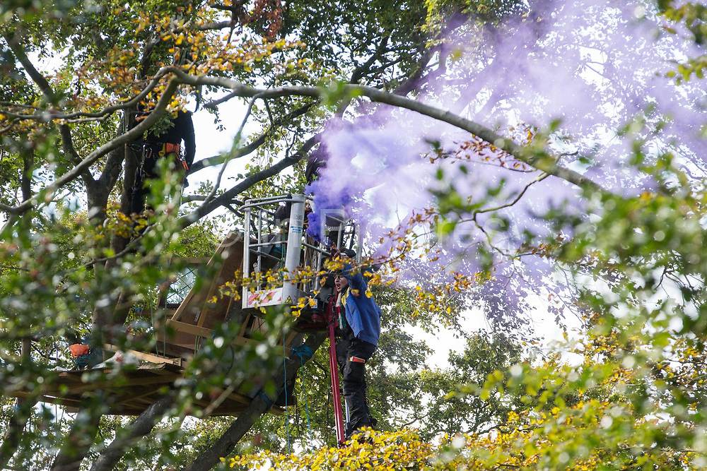 An anti-HS2 tree protector with a smoke grenade climbs onto the arm of a cherry picker being used by National Eviction Team bailiffs working on behalf of HS2 Ltd to dismantle his tree house at a wildlife protection camp in ancient woodland at Jones' Hill Wood on 1 October 2020 in Aylesbury Vale, United Kingdom. Around 40 environmental activists and local residents, some of whom living in makeshift tree houses 60 feet above the ground, were present during the evictions at Jones' Hill Wood which had served as one of several protest camps set up along the route of the £106bn HS2 high-speed rail link in order to resist the controversial infrastructure project.