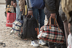 Licensed to London News Pictures. 10/11/2016. Mosul, Iraq. Iraqi men, holding bags containing their possessions, wait in line as the prepare to board a bus that will evacuate them from Mosul's Gogjali District. The bus, provided by the Iraqi Army, will take them away from the fighting in the city to the safety of a refugee camp in Iraqi-Kurdistan.<br /> <br /> The battle to retake Mosul, which fell June 2014, started on the 16th of October 2016 with Iraqi Security Forces eventually reaching the city on the 1st of November. Since then elements of the Iraq Army and Police have succeeded in pushing into the city and retaking several neighbourhoods allowing civilians living there to be evacuated - though many more remain trapped within Mosul. Photo credit: Matt Cetti-Roberts/LNP