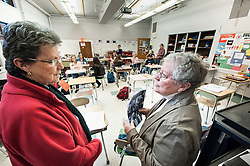 Sisters Claudette Saunders and Lorraine Benoit chat before engaging in a dialogue with students at Laconia High School on Thursday, December 20, 2012.  (Alan MacRae/for the Laconia Daily Sun)