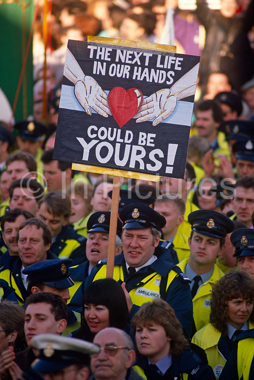 A crowd of striking ambulance drivers and other health service personnel gather in Trafalgar Square in central London to protest over poor working conditions. A placard showing a pair of hands holding a human heart telling us that they are important public serve because they help save lives. But unclean ambulances, one-hour queues to drop patients off at A&E departments and 12-hour shifts with little or no breaks about pay lowered staff morale so that paramedics implemented a work-to-rule policy to protest about a lack of resources. Ambulance workers enjoyed unprecedented levels of public support during the six-month dispute as opinion polls found more than four out of five people consistently backed the unions.