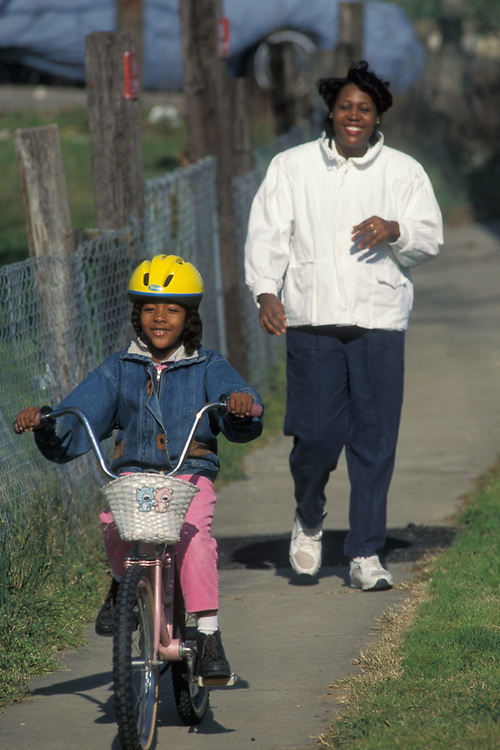 African-American mother running after daughter on bicycle on sidewalk in Austin, Texas.  Model Release.<br /> ©Bob Daemmrich