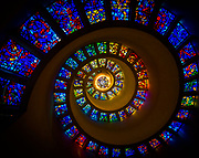The Chapel of Thanksgiving is a small, spiral tower that features an enclave for prayerful thanks. The entrance to the chapel is at the end of a 125-foot (38 m) bridge that runs over a cascading waterfall. Inside the chapel, the spiral is topped with stained glass windows, leaving a flood of color when looking up in the chapel. Collectively, the stained glass, which was designed by Gabriel Loire of Chartres, France is called the Glory Window. It was designed to feature brighter colors as the spiral reached its apex, becoming brighter and brighter as it reached the center.