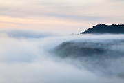 A temperature inversion partially covers The Roaches, as seen from Ramshaw Rocks. Staffordshire, Peak District, England, UK.