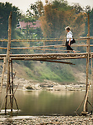 "12 MARCH 2016 - LUANG PRABANG, LAOS:  A tourist walks across a bamboo bridge spanning the Nam Khan River in Luang Prabang. Luang Prabang was named a UNESCO World Heritage Site in 1995. The move saved the city's colonial architecture but the explosion of mass tourism has taken a toll on the city's soul. According to one recent study, a small plot of land that sold for $8,000 three years ago now goes for $120,000. Many longtime residents are selling their homes and moving to small developments around the city. The old homes are then converted to guesthouses, restaurants and spas. The city is famous for the morning ""tak bat,"" or monks' morning alms rounds. Every morning hundreds of Buddhist monks come out before dawn and walk in a silent procession through the city accepting alms from residents. Now, most of the people presenting alms to the monks are tourists, since so many Lao people have moved outside of the city center. About 50,000 people are thought to live in the Luang Prabang area, the city received more than 530,000 tourists in 2014.      PHOTO BY JACK KURTZ"