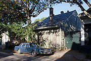 An old American car outside a traditional New Orleans wooden house in the evening light, street secene, New Orleans, Louisiana, USA.