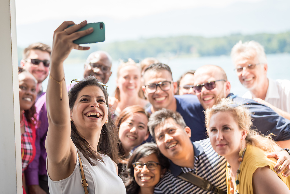 """1 July 2018, Geneva, Switzerland: Following Sunday service at the Evangelical Lutheran Church in Geneva, LWF Council members journeyed from Geneva to Nyon by boat across Lake Geneva. The 2018 LWF Council meeting takes place in Geneva from 27 June - 2 July. The theme of the Council  is """"Freely you have received, freely give"""" (Matthew 10:8, NIV). The LWF Council meets yearly and is the highest authority of the LWF between assemblies. It consists of the President, the Chairperson of the Finance Committee, and 48 members from LWF member churches in seven regions. Here, Sally Azar from the The Evangelical Lutheran Church in Jordan and the Holy Land (PALESTINE) takes a group photo with the council's young members, LWF general secretary Rev. Dr Martin Junge and LWF president Archbishop Musa Panti Filibus."""