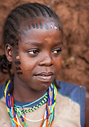 Scary Scarifications<br /> <br /> Seeing a scarification ceremony in the Surma tribe from the Omo valley in Ethiopia is a tough time. Not for the girl who is going to be scarified but for the foreigner who needs to see blood running, flies going into the wounds, under a hard sun. The girl, who was 12, did NOT say any word during the ten minutes ceremony, and did NOT show any pain. Her mother used a spine to pull the skin and a razor blade to cut the skin. <br /> At the end, i asked her if it was not too hard to have her skin cut with a razor blade, and she answered that she was close to collapse! It was incredible as she did not show any sign of pain on her face. It would be a shame for the family she confessed. A girl's eagerness to tolerate pain is also an indication of her emotional maturity and willingness to bear children.<br /> The kid chooses to do it, nobody obliged her. Scarifications are a beauty sign in the tribes. This is the tradition in Surma tribe.<br /> But for years now, the kids who go to school or who convert to christian, are told not to do it anymore. The men say the lack of scars on the skins make them looking ugly.<br /> The skin of the tribes in this area has a special reaction to cutting: the cicatrisation creates raising scars. Ash and certain organic saps might be added to a wound to make the scarring more prominent and or embellished.<br /> Not far from the Surma area, the Bodi women also make scars, some even have coil scarifications on the shoulders. It is very painful as they use some metal to do this, like when they do it to their cows to mark them on the fur and the skin! Pain seems unknown in the area.<br /> I met Ana who lives in the small village of Hana Mursi. She now hides her scarifications she had at 12, as she has gone to Arba Minch town to study at the Police school. People wearing scarifications are seen as « primitives » by many urban ethiopians and they suffer from this. She is proud to introduce me to her best friend, a bodi teenager who has made a heart on her a