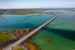 Aerial view from drone of Benbecula road causeways crossing estuaries and joining small islands across Benbecula in  the Outer Hebrides, Scotland, UK