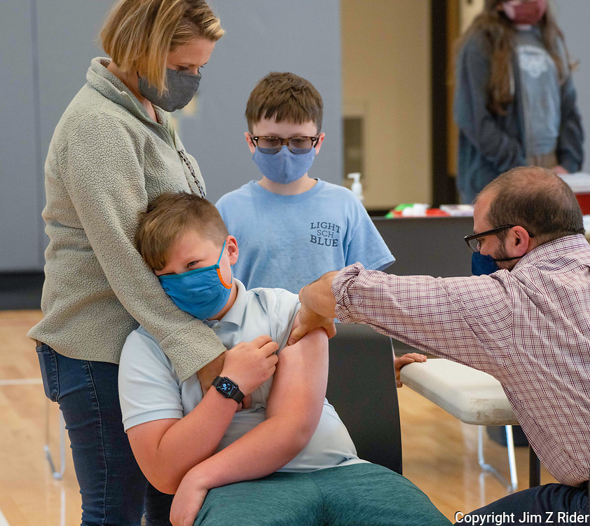 Henry Cantlin, 12, of Erdenheim, Pennsylvania, leans on his mother Catherine for support as he receives a Covid-19 vaccination at the Greene Street Friends School in the Germantown neighborhood of Philadelphia, PA.  His brother Walter, 9, looks on.