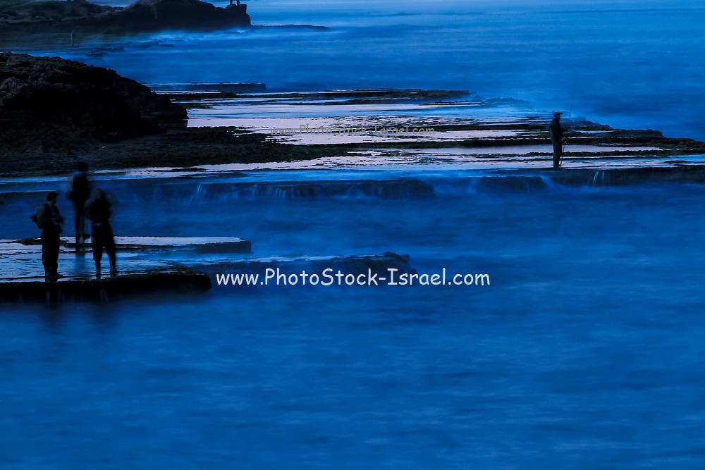 Silhouette of fishermen fishing off rocks in the Mediterranean Sea, Achziv, Israel