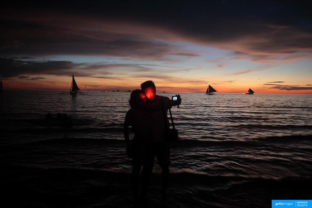 Asian tourists take a self portrait during sunset at White Beach,  Boracay Island, the Philippines on October 3, 2008, Photo Tim Clayton.....Asian tourists at White Beach, Boracay Island, the Philippines...The 4 km stretch of White beach on Boracay Island, the Philippines has been honoured as the best leisure destination in Asia beating popular destinations such as Bali in Indonesia and Sanya in China in a recent survey conducted by an International Travel Magazine with 2.2 million viewers taking part in the online poll...Last year, close to 600,000 visitors visited Boracay with South Korea providing 128,909 visitors followed by Japan, 35,294, USA, 13,362 and China 12,720...A popular destination for South Korean divers and honeymooners, Boracay is now attracting crowds of tourists from mainland China who are arriving in ever increasing numbers. In Asia, China has already overtaken Japan to become the largest source of outland travelers...Boracay's main attraction is 4 km of pristine powder fine white sand and the crystal clear azure water making it a popular destination for Scuba diving with nearly 20 dive centers along White beach. The stretch of shady palm trees separate the beach from the line of hotels, restaurants, bars and cafes. It's pulsating nightlife with the friendly locals make it increasingly popular with the asian tourists...The Boracay sailing boats provide endless tourist entertainment, particularly during the amazing sunsets when the silhouetted sails provide picture postcard scenes along the shoreline...Boracay Island is situated an hours flight from Manila and it's close proximity to South Korea, China, Taiwan and Japan means it is a growing destination for Asian tourists... By 2010, the island of Boracay expects to have 1,000,000 visitors.