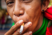 14 OCTOBER 2012 - BANGKOK, THAILAND:  A man smokes a cigarette on a street in Bangkok, Thailand. Thailand and the Philippines are involved in a dispute over cigarette taxes. Philippine trade officials allege that Thailand charges an unfair import tax on Philippine cigarettes. Thai officials have responded that they have taken the matter under advisement. Philippine officials said they may take the issue to the World Trade Organization if Thailand doesn't respond by Oct. 15.   PHOTO BY JACK KURTZ
