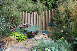 Table and chairs in courtyard garden. Wooden posts used as fence. Beyond the Pale Garden. Design: Stephen Firth and Brinsbury students - Chelsea 2005