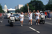 The Olympic torch is carried through the streets of Washington, DC from the US Capitol building as part of the relay to the 1996 Summer Games in Atlanta June 21, 1996.