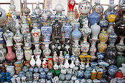 Ceramic pots for sale in the indoor antique market in Yu Yuan Garden, downtown Shanghai, China. The pots and ceramics being sold by this family business on the top floor of the market are not genuine antiques. Many are fakes, which are sold to the more gullible tourists. Genuine antiques can be bought but the prices reflect their age considerably.