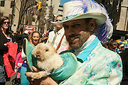 A man in bright outfit with a rabbit in a hat.