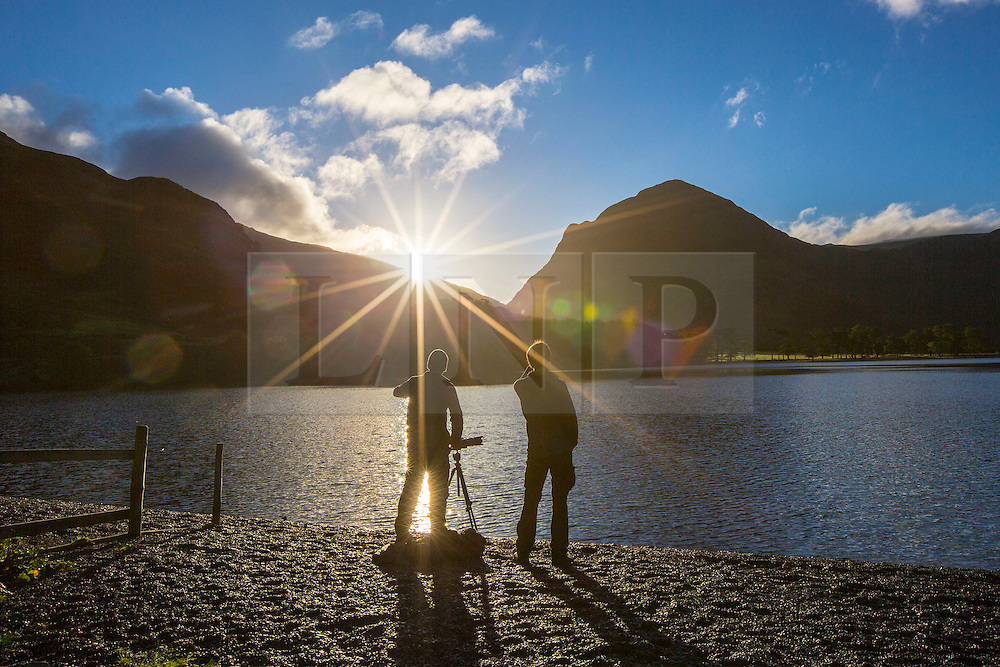 © Licensed to London News Pictures. 02/10/2016. Buttermere UK. Picture shows Amatuer photographers gathered at Buttermere lake in Cumbria to capture this morning's sunrise. Photo credit: Andrew McCaren/LNP