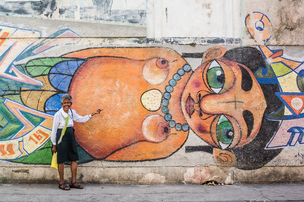 A woman stands with a wall mural on the street of Havana, Cuba