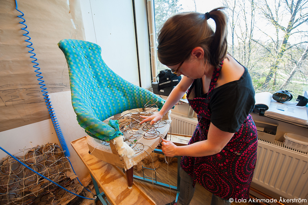 A furniture upholstery student working on a chair.