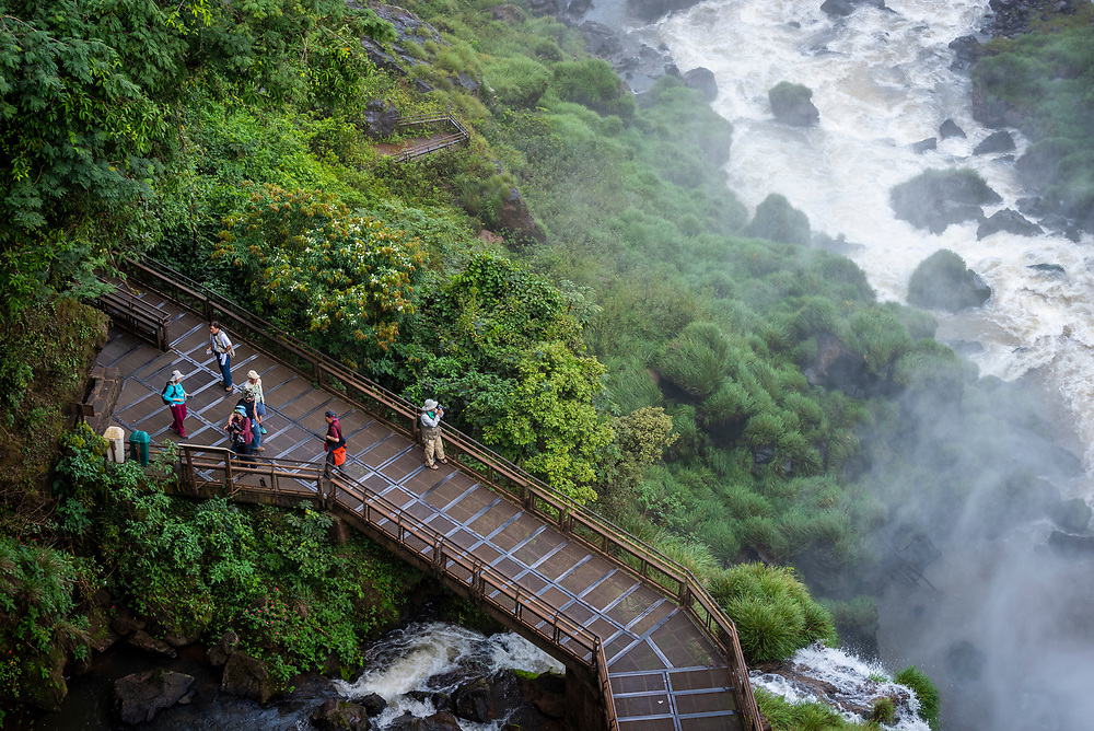 High angle view of tourists walking the lower circuit trail at Salto Bossetti at Iguazu National Park in Argentina.<br /> (March 30, 2019)