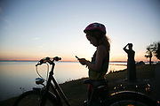 A young girl is catching pokemons by the sea at sun set in landskrona, Sweden, 27th of August 2016. A statues looks out to see in the back ground.