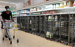 © Licensed to London News Pictures. 03/08/2021. London, UK. A shopper wearing a face covering walks past empty trolleys of fresh milk in Sainsbury's, north London. It has been reported that Britain could face a shortage of milk supplies and these are likely to continue for several months, due to a lack of lorry drivers. UK's biggest milk processor, Arla Foods UK, has said that a number of individual stores have missed deliveries due to the pingdemic. Photo credit: Dinendra Haria/LNP