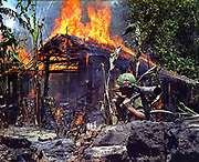 My Tho, Vietnam. A Burning Vietcong Base Camp. In the foreground is Private First Class Raymond Rumpa, St Paul, Minnesota, C Company, 3rd Battalion, 47th Infantry, 9th Infantry Division, with 45 pound 90mm recoiless rifle, 4 May 1968.