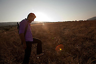 An FSA soldier walks through a field surrounding the town of Basheria, Idlib province in Syria's northwest. Idlib province in Syria's northwest is one of the few areas in Syria which is currently under FSA control, although this control is patchy and ever shifting. Basheria, Idlib, Syria. 19/06/2012