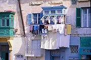 Woman hanging washing to dry from window in old housing area of Valletta, Malta 1978