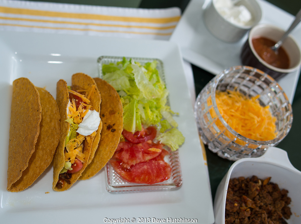 Homemade hard-shell corn tortilla tacos on a plate showing the ingredients including ground beef, shredded cheese, lettuce, tomato, sour cream, and salsa.