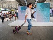 """27 MARCH 2015 - BANGKOK, THAILAND: A shopper on the skywalk that connects Emporium to """"EmQuartier,"""" a new shopping mall in Bangkok. """"EmQuartier"""" is across Sukhumvit Rd from Emporium. Both malls have the same corporate owner, The Mall Group, which reportedly spent 20Billion Thai Baht (about $600 million US) on the new mall and renovating the existing Emporium. EmQuartier and Emporium have about 450,000 square meters of retail, several hotels, numerous restaurants, movie theaters and the largest man made waterfall in Southeast Asia. EmQuartier celebrated its grand opening Friday, March 27.   PHOTO BY JACK KURTZ"""