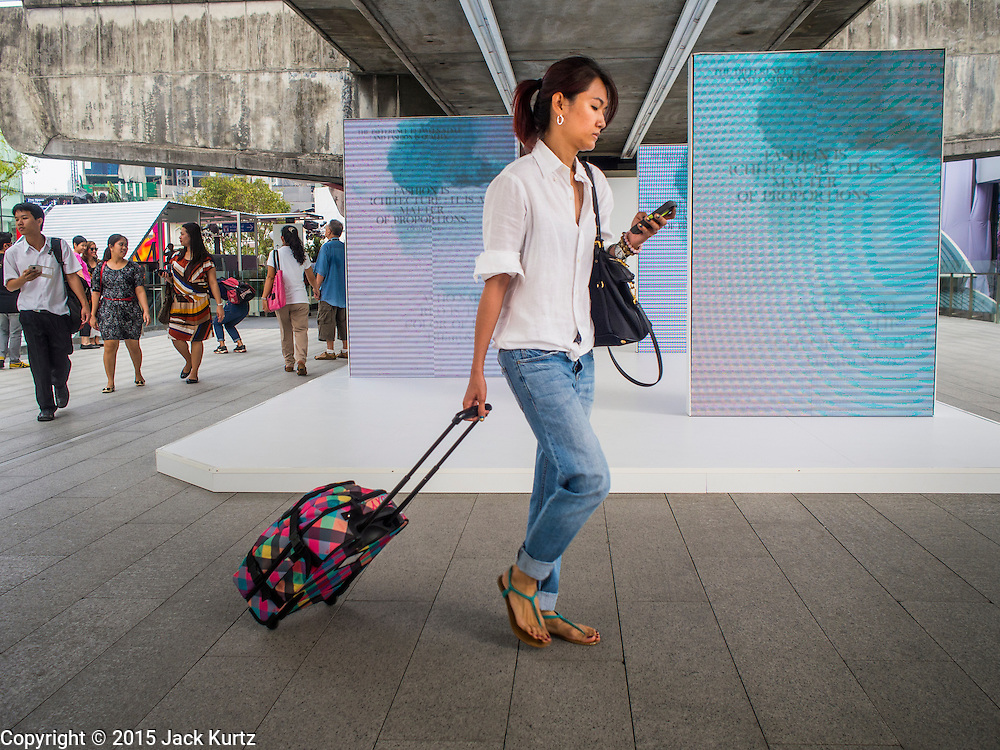 "27 MARCH 2015 - BANGKOK, THAILAND: A shopper on the skywalk that connects Emporium to ""EmQuartier,"" a new shopping mall in Bangkok. ""EmQuartier"" is across Sukhumvit Rd from Emporium. Both malls have the same corporate owner, The Mall Group, which reportedly spent 20Billion Thai Baht (about $600 million US) on the new mall and renovating the existing Emporium. EmQuartier and Emporium have about 450,000 square meters of retail, several hotels, numerous restaurants, movie theaters and the largest man made waterfall in Southeast Asia. EmQuartier celebrated its grand opening Friday, March 27.   PHOTO BY JACK KURTZ"