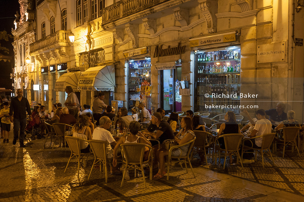 The busy Cafe Montanha in Largo da Portagem at night in Coimbra, Portugal.