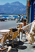 Calvi, Corsica, France in late 1950s fisherman mending nets at seafront cafe